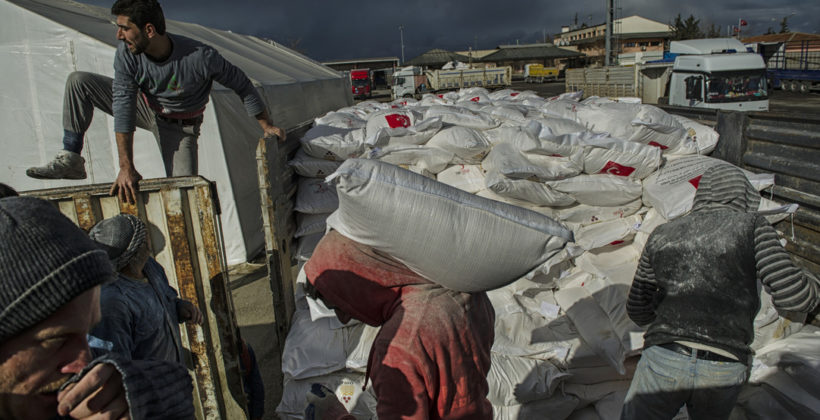 Tonnes of flour are loaded into trucks to be delivered to Syrian refugees