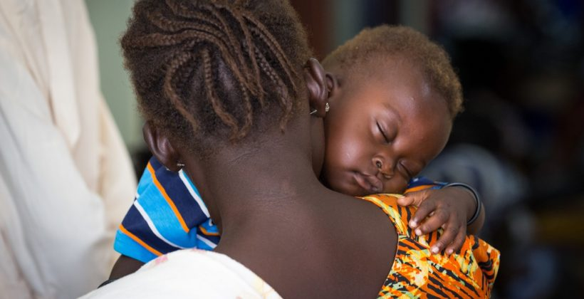 A baby sleeps on her mother's shoulder in South Sudan