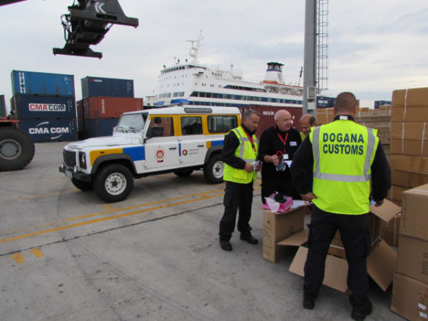 Albanian customs staff checking crates.