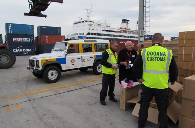 Albanian customs staff checking crates.