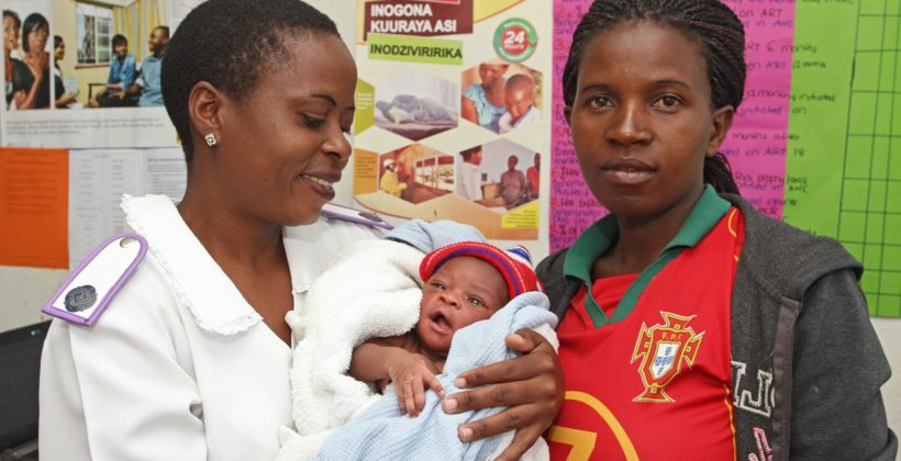 Zimbabwean midwife holding a woman's baby.