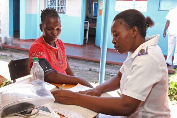 Zimbabwean nurse taking down someone's details.