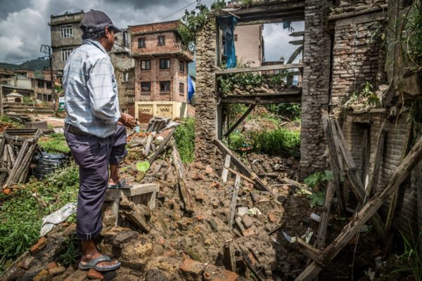 Man surveying a destroyed dwelling in Nepal.