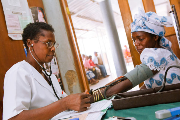 Nurse Oby Osigwe conducting triage with a patient at Saint Mary catholic hospital in Abuja, one of the hospitals benefiting from NACA support in Nigeria.