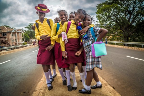 Schoolgirls in Sierra Leone standing in the road.