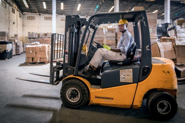 Warehouse worker riding a forklift.