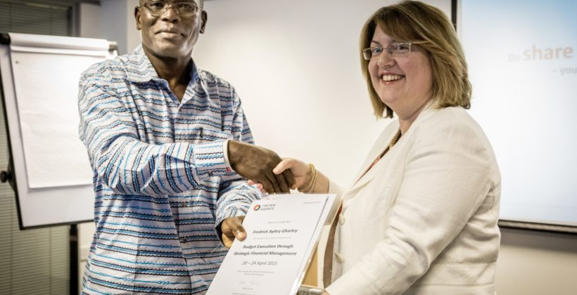 A man accepting a certificate from a woman at a training event.