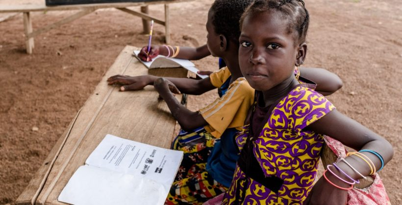 A Ghanaian schoolgirl sitting at her desk and looking at the camera.