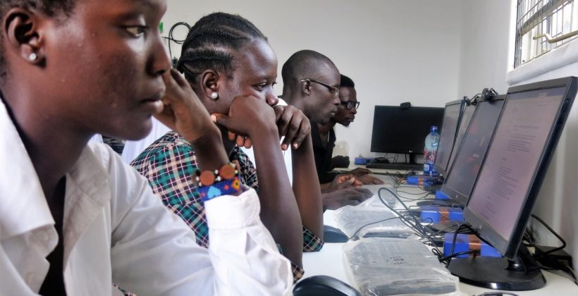 A row of people looking at computers in the Kakuma Refugee camp ICT hub.