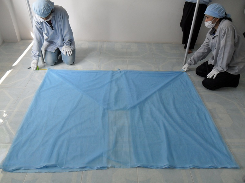 Two staff wearing protective equipment inspecting a bed net.